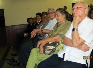 Clive smiles approvingly at the showing of the video seated next to him (left) is his wife Patsy and Father Gervais Girod a former Dean and to his right, former Principal Mervyn Moore